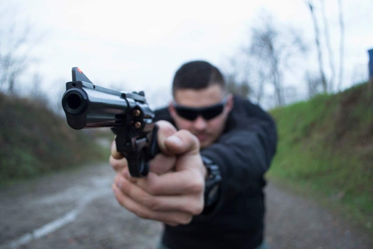 mężczyzna strzela z rewolweru alfa proj 357magnum w czarnych okularach fabryka strzelania
